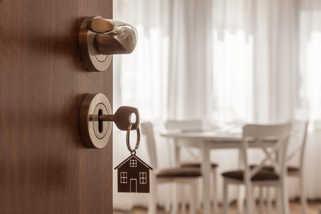 Open Door To A New Home. Door Handle With Key And Home Shaped Ke